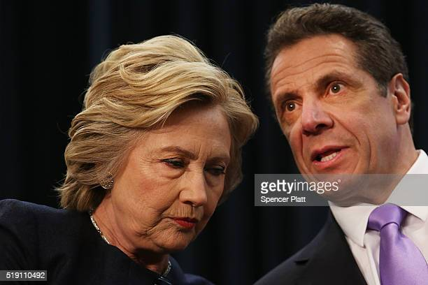 Democratic presidential candidate Hillary Clinton speaks with New York Governor Andrew Cuomo at a rally with after he signed a law that will...