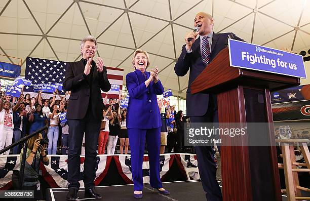 Democratic presidential candidate Hillary Clinton stands on stage with singer Jon Bon Jovi and US Senator Cory Booker at a rally on June 1 2016 in...