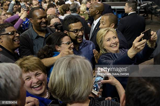 TOPSHOT Democratic presidential candidate Hillary Clinton takes a selfie with an attendee after addressing a rally on March 12 2016 in Youngstown...