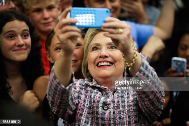 Democratic presidential candidate Hillary Clinton takes photographs with supporters after a campaign rally at Sacramento City College on June 5 2016...