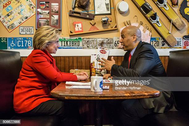 Democratic presidential candidate Hillary Clinton talks with Sen Cory Booker at Riley's Cafe on January 24 2016 in Cedar Rapids Iowa The Democratic...