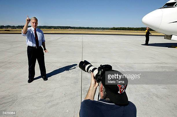 Democratic presidential candidate Howard Dean jokes with a photographer on the tarmac at Portland Airport during his Sleepless Summer Tour August 24...