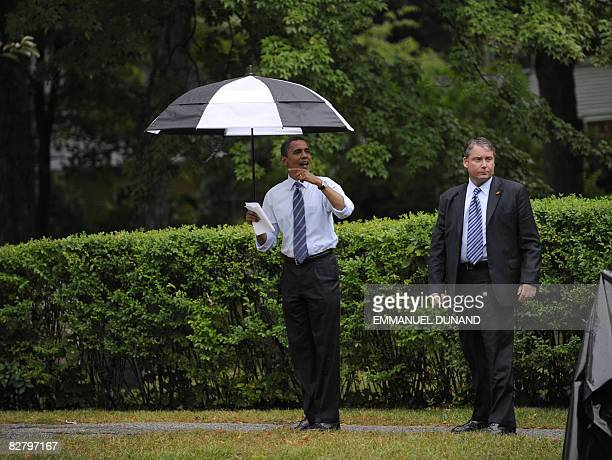 US Democratic presidential candidate Illinois Senator Barack Obama tells supporters that he is late as he walks protected from rain by an umbrella on...