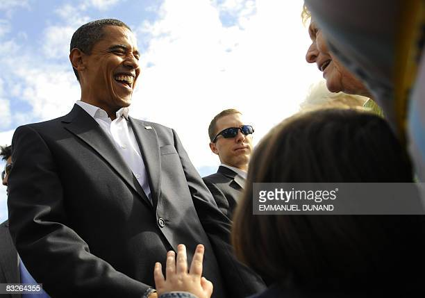 US Democratic presidential candidate Illinois Senator Barack Obama laughs with a supporter after her granddaughter mistook him for Republican rival...
