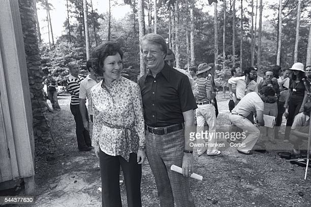 Democratic presidential candidate Jimmy Carter stands with his wife Rosalynn while members of the media gather behind them during Carter's campaign...