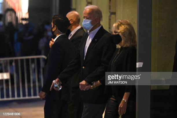 Democratic Presidential candidate Joe Biden holds hands with wife Jill Biden as he leaves after speaking at the Queen venue in Wilmington, Delaware,...