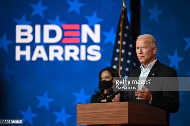 Democratic Presidential candidate Joe Biden speaks as US Senator and Vice-Presidential candidate, Kamala Harris, looks on at the Queen venue in...