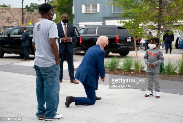 Democratic Presidential Candidate Joe Biden speaks C.J. Brown , the owner's son, as he shops for his grandkids at the Three Thirteen store in...