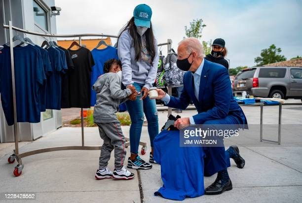 Democratic Presidential Candidate Joe Biden talks with a young boy as he shops at the Three Thirteen store in Detroit, Michigan, on September 9, 2020.