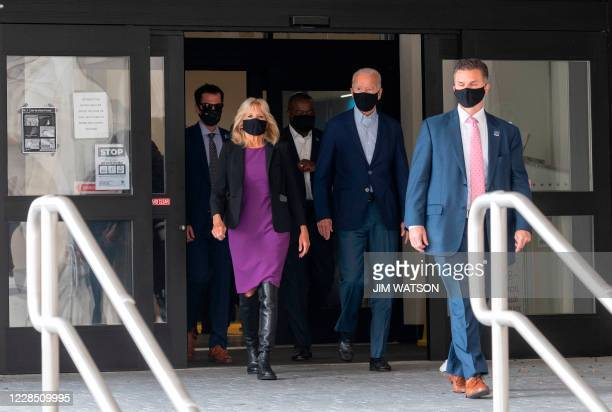 Democratic presidential candidate Joe Biden walks out of the state building with his wife Jill, after voting in the Delaware state primary in...