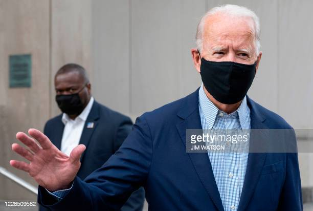Democratic presidential candidate Joe Biden waves as he walks out of the Delaware State Building, after voting in the Delaware state primary in...
