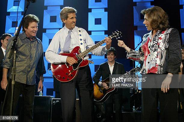 Democratic presidential candidate John Kerry plays the guitar as his wife Teresa Heinz and musician John Foggerty look on at a Kerry/Edwards 2004...