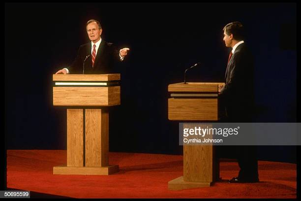 Democratic presidential candidate Michael Dukakis poised podiumside facing his pointmaking Republican opponent VP George Bush in first debate