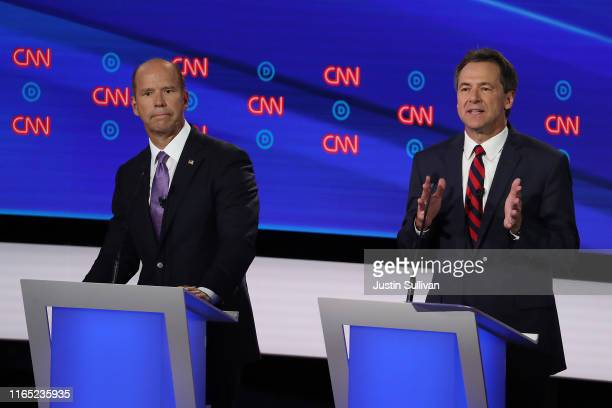 Democratic presidential candidate Montana Gov. Steve Bullock speaks while former Maryland congressman John Delaney listens during the Democratic...