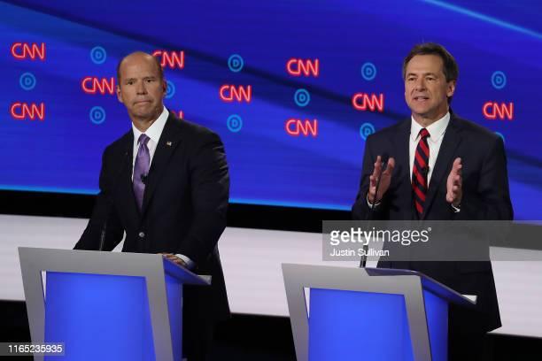 Democratic presidential candidate Montana Gov Steve Bullock speaks while former Maryland congressman John Delaney listens during the Democratic...