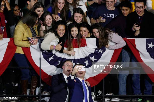 Democratic presidential candidate Pete Buttigieg takes a selfie with his husband Chasten Buttigieg and supporters after addressing his caucus night...