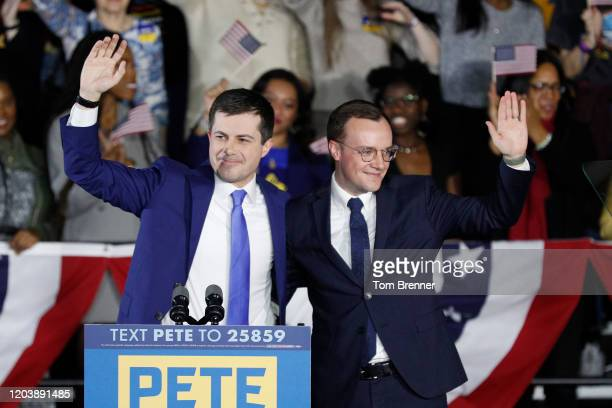 Democratic presidential candidate Pete Buttigieg waves with his husband Chasten Buttigieg after addressing supporters at his caucus night watch party...