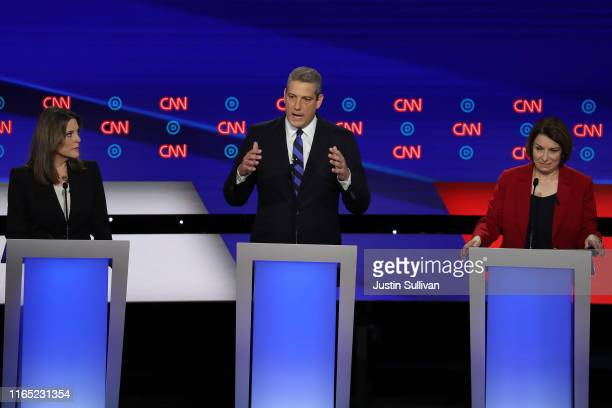 Democratic presidential candidate Rep. Tim Ryan speaks while Sen. Amy Klobuchar and Marianne Williamson listen during the Democratic Presidential...