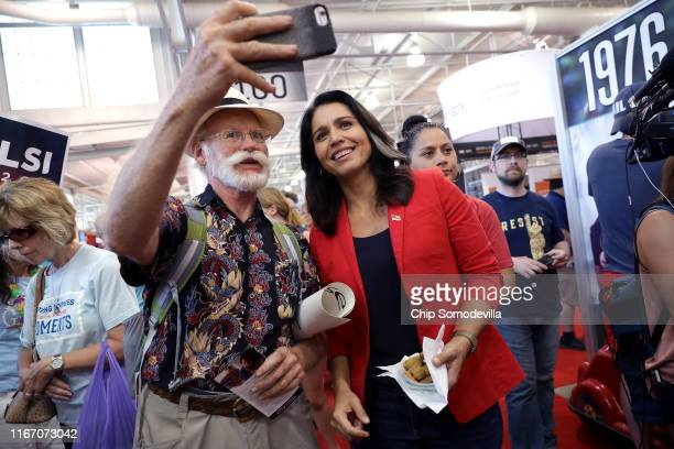 Democratic presidential candidate Rep Tulsi Gabbard poses for a selfie with a supporter during the Iowa State Fair August 09 2019 in Des Moines Iowa...