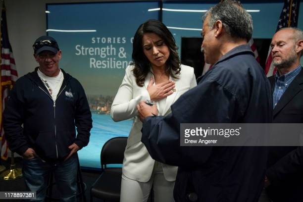 Democratic presidential candidate Rep Tulsi Gabbard talks with family members of 9/11 victims following a press conference at the 9/11 Tribute Museum...