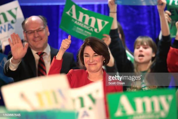 Democratic presidential candidate Sen Amy Klobuchar addresses supporters as her husband John Bessler looks on at her caucus night watch party before...