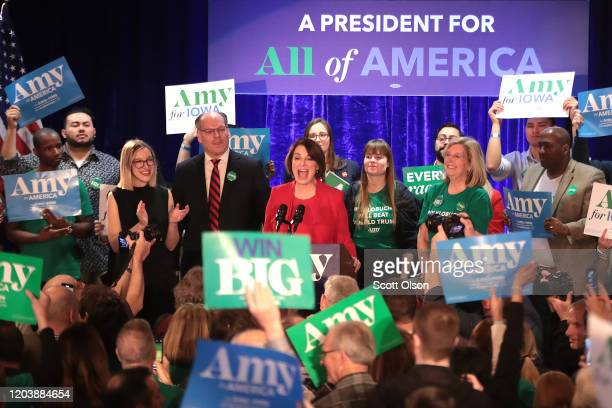 Democratic presidential candidate Sen. Amy Klobuchar addresses supporters, as her husband John Bessler and daughter Abigail look on, at her caucus...