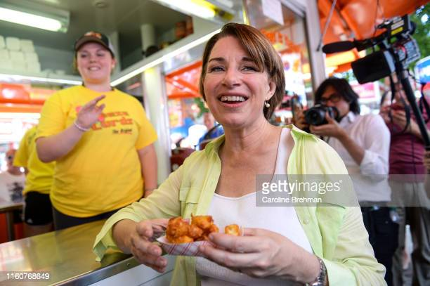 Democratic presidential candidate Sen. Amy Klobuchar, D-Minn., grabs a basket of cheese curds at the Iowa State Fair on Saturday August 10, 2019.