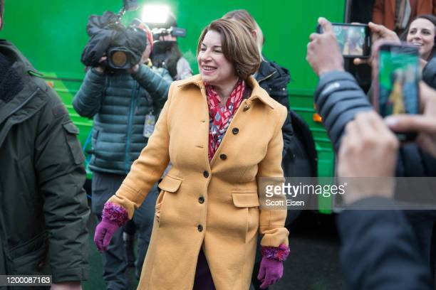 Democratic presidential candidate Sen Amy Klobuchar reacts as she gets off her campaign bus to visit the polling location at Webster Elementary...