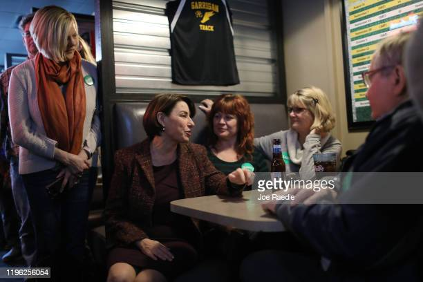 Democratic presidential candidate Sen Amy Klobuchar talks with Michelle Simpson and Marilyn Simpson during a campaign stop at Miller's Sports Bar and...