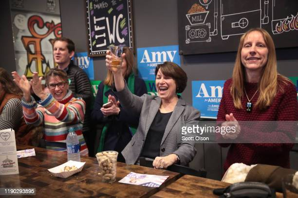 Democratic presidential candidate Sen Amy Klobuchar toasts the birthday of one of her campaign staff members during a campaign stop at Timbukbru brew...