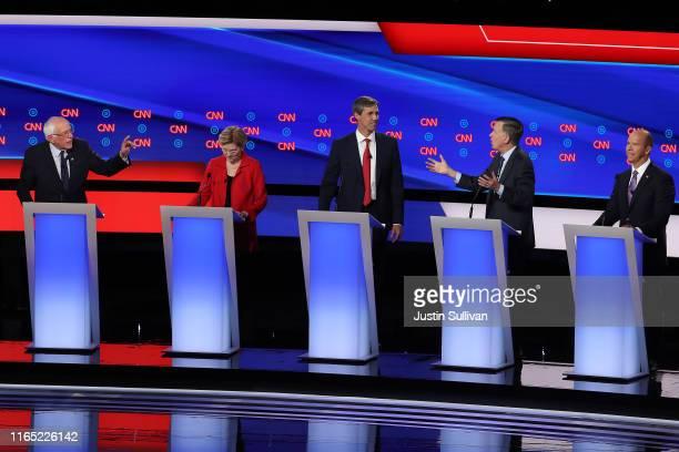Democratic presidential candidate Sen Bernie Sanders and former Colorado governor John Hickenlooper speaks while Sen Elizabeth Warren former Texas...