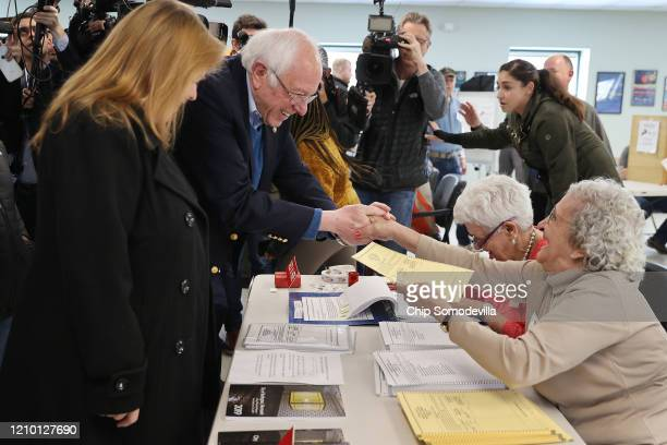 Democratic presidential candidate Sen. Bernie Sanders and his wife Jane O'Meara Sanders greet poll workers before voting in their state's primary...
