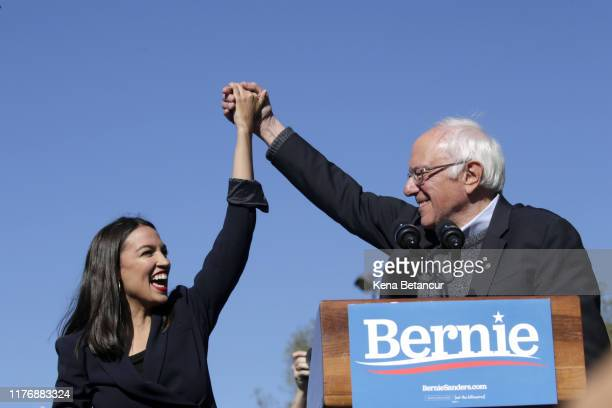 Democratic presidential candidate Sen Bernie Sanders holds hands with Rep Alexandria OcasioCortez during his speech at a campaign rally in...