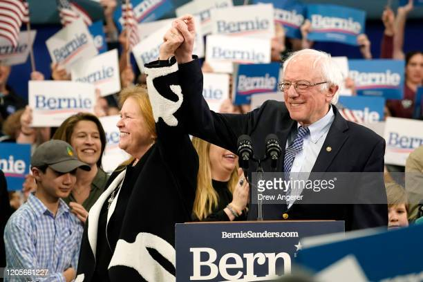 Democratic presidential candidate Sen. Bernie Sanders holds the hand of his spouse Jane O'Meara Sanders as he takes the stage during a primary night...