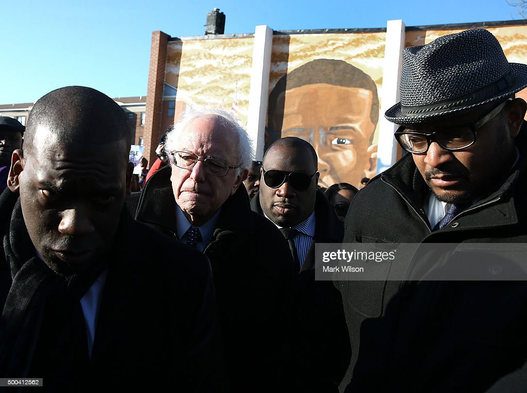 Democratic presidential candidate Sen. Bernie Sanders, (I-VT)(2ndL) is escorted during a tour of Sandtown-Winchester Neighborhood where Freddie Gray lived and was arrested, December 8, 2015 in Baltimore, Maryland. Sen. Sanders later met with African-American religious and civic leaders.