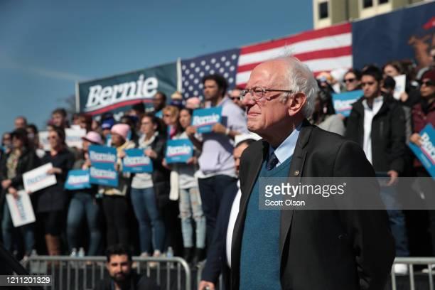 Democratic presidential candidate Sen. Bernie Sanders listens as Rev. Jesse Jackson addresses the crowd during Sander's campaign rally in Calder...