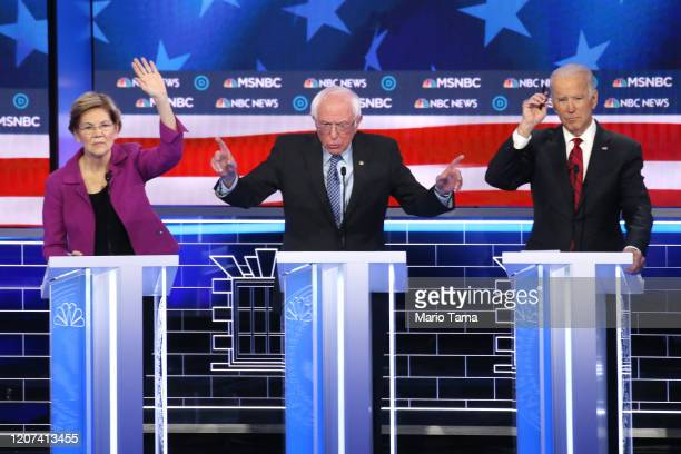 Democratic presidential candidate Sen Bernie Sanders makes a point as Sen Elizabeth Warren and former Vice President Joe Biden raise their hands...