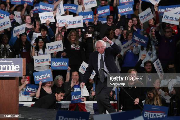 Democratic presidential candidate Sen Bernie Sanders makes it to the stage to address supporters with his wife Jane Sanders during his caucus night...