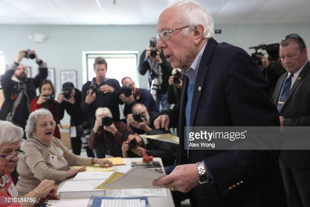 Democratic presidential candidate Sen Bernie Sanders picks up a ballot from the checkin counter at a polling place March 3 2020 at Robert Miller...
