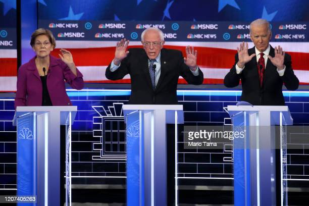Democratic presidential candidate Sen Bernie Sanders speaks as former Vice President Joe Biden and Sen Elizabeth Warren react during the Democratic...