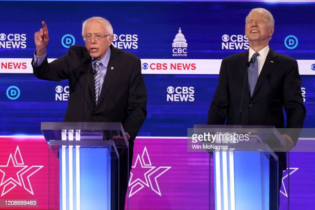 Democratic presidential candidate Sen Bernie Sanders speaks as former Vice President Joe Biden reacts during the Democratic presidential primary...