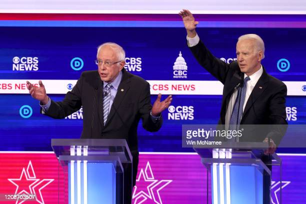Democratic presidential candidate Sen Bernie Sanders speaks as former Vice President Joe Biden reacts during the Democratic presidential primary...