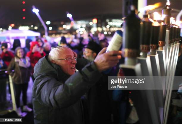 Democratic presidential candidate Sen Bernie Sanders uses a torch to light a Menorah during a lighting event at the Chanukah on Ice campaign event at...