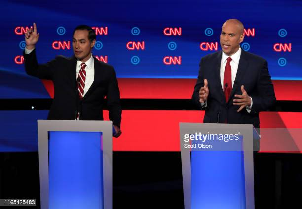 Democratic presidential candidate Sen Cory Booker speaks while former housing secretary Julian Castro listen raises his hand during the Democratic...
