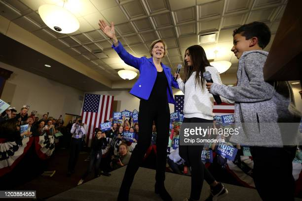 Democratic presidential candidate Sen Elizabeth Warren addresses supporters with her grandchildren Atticus Mann Tyagi and Lavinia Tyagi during her...