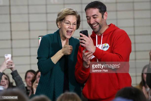 Democratic presidential candidate Sen Elizabeth Warren and supporter Jason Klokkenga speak with Klokkenga's mother via mobile phone during a town...