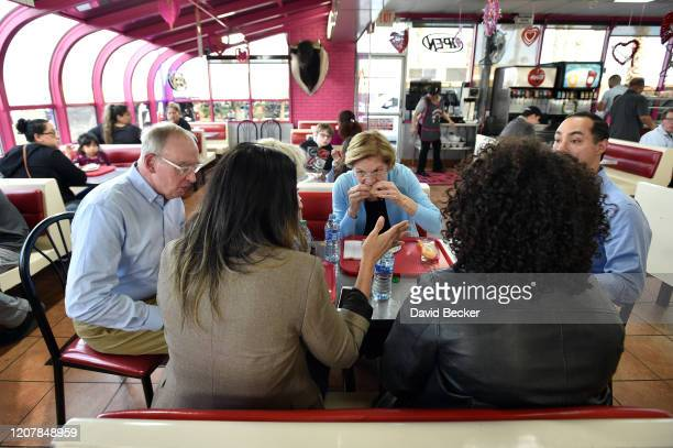 Democratic presidential candidate Sen. Elizabeth Warren has a bite with people including her husband Bruce Mann and former Secretary of Housing and...