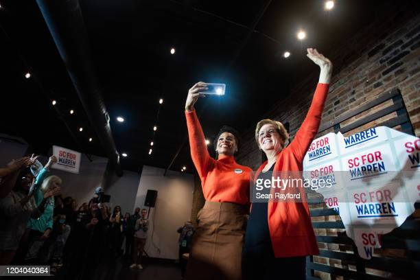 Democratic presidential candidate Sen. Elizabeth Warren , right, waves to the crowd as actress Anika Noni Rose takes a selfie during a canvassing...