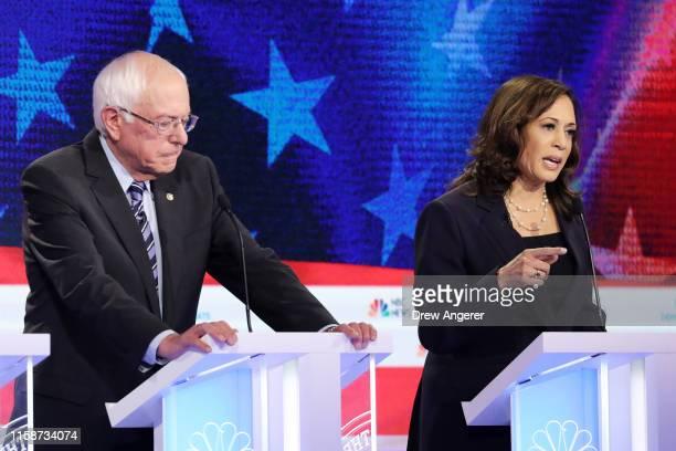 Democratic presidential candidate Sen Kamala Harris speaks as Sen Bernie Sanders looks on during the second night of the first Democratic...