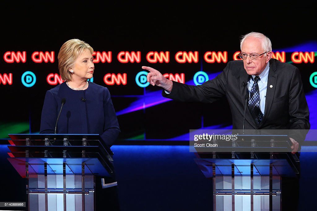 /Democratic presidential candidate Senator Bernie Sanders (D-VT) speaks as Democratic presidential candidate Hillary Clinton looks on during the CNN Democratic Presidential Primary Debate at the Whiting Auditorium at the Cultural Center Campus on March 6, 2016 in Flint, Michigan. Voters in Michigan will go to the polls March 8 for the state's primary.